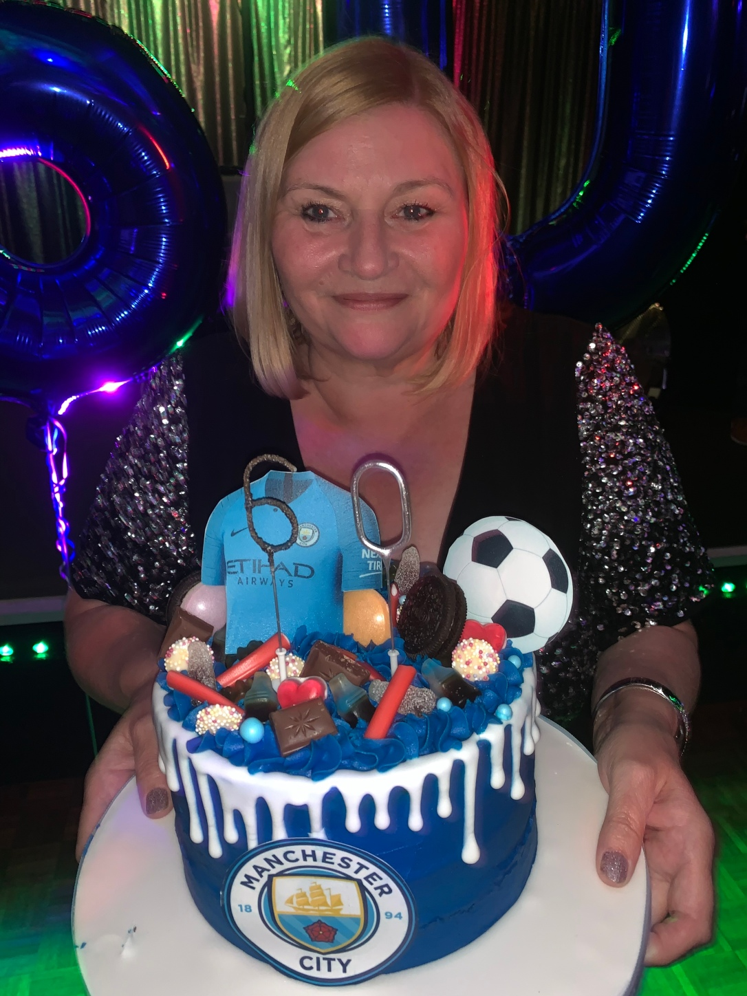 Nicola's mum holding her birthday cake in front of huge number balloons 6 and 0.